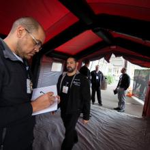 JPS Emergency Management team members inspect a COVID-19 screening tent.